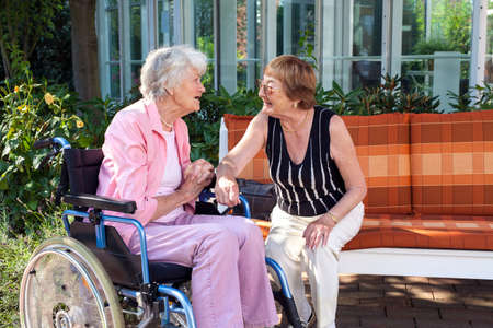 social care: Two senior ladies chatting on a garden bench with one sitting in a wheelchair at the end as they enjoy a day outdoors in the shade of a tree