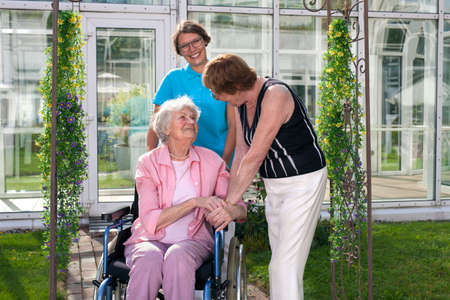 caregivers: Two Health Care Professionals for Old Age Patient on Wheel Chair. Captured at Home Care Garden.