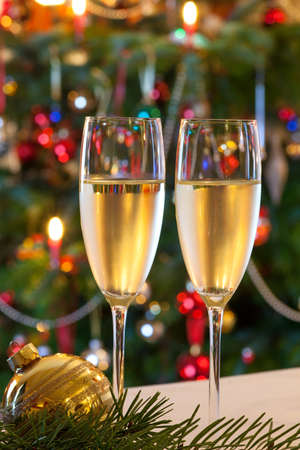 solemnity: Christmas composition as still life with two glasses of champagne and a golden christmas glitter ball on fir branch. On background a christmas tree. Stock Photo