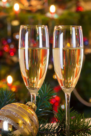Christmas still life with champagne, golden christmas ball on fir branch and christmas tree with colorful decoration in background. photo
