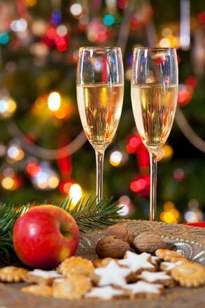 solemnity: Christmas composition with two glasses of champagne, standing on table behind a plate, decorated with cookies and apple. Background colorful christmas tree.