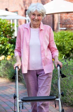 Oudere dame met een rollator in de tuin die zich op een pad met gebouwen op de achtergrond lachend naar de camera