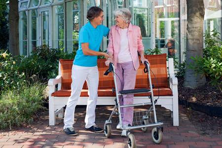 Oudere vrouw met behulp van een loophulpmiddel met de hulp van haar liefhebbende dochter of verpleeghulp genieten van een dag in het park met een glazen serre op de achtergrond