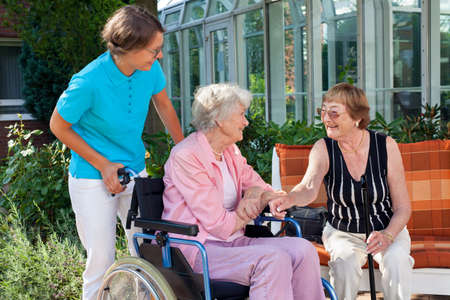 pushed: Elderly lady sitting in a wheelchair being pushed by a carer pausing to talk to a friend who is sitting on a wooden garden bench