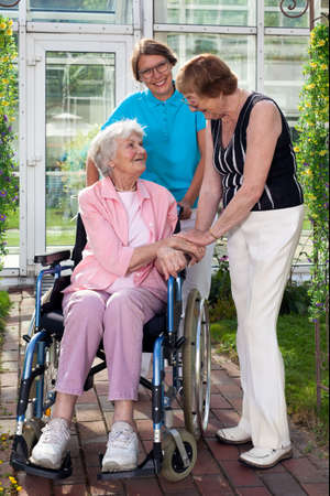 Close up Elderly Patient on Wheel Chair with Two Caregivers Captured at Garden with Glass Building at the Back. Stock Photo