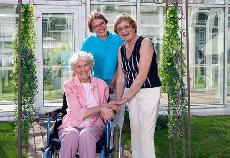Gelukkig Mantelzorgers voor Ouderen Patiënt bij Home Garden Kijkend naar de camera. Gevangen met Glas Bouw op de achtergrond. Stockfoto