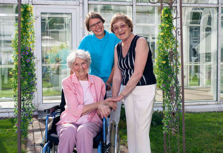 gracious: Happy Caregivers for Elderly Patient at Home Garden Looking at Camera. Captured with Glass Building at the Background.