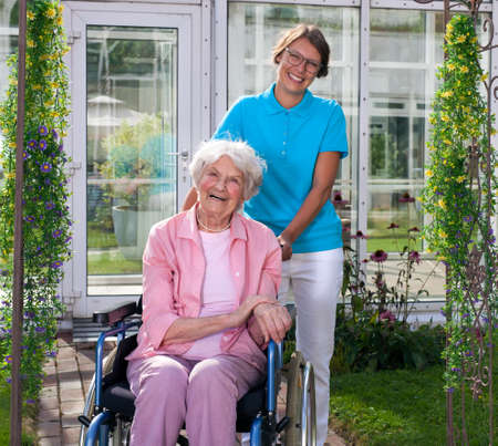 Female professional carer or middle-aged daughter behind happy elderly woman in wheelchair, in a green garden