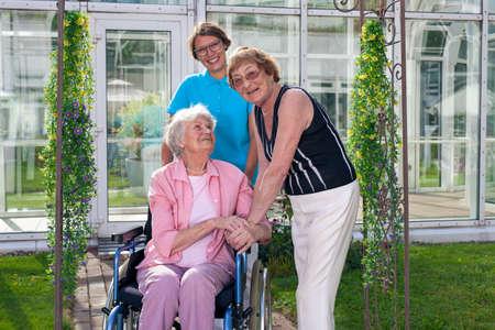 Twee glimlachende verzorgers, kijken naar camera, voor Old Age Patiënt op rolstoelen. Gevangen bij Grassy Green Garden met glazige Home Care Building Achtergrond. Stockfoto