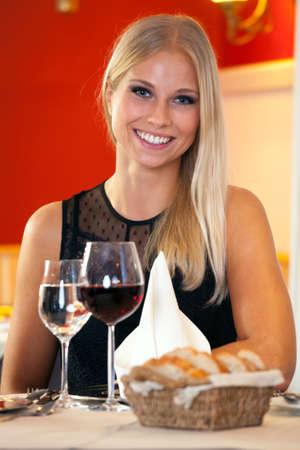 Beautiful blond young woman smiling at camera while sitting at a table in a fancy restaurant, with two glasses with white and red wine in front of her