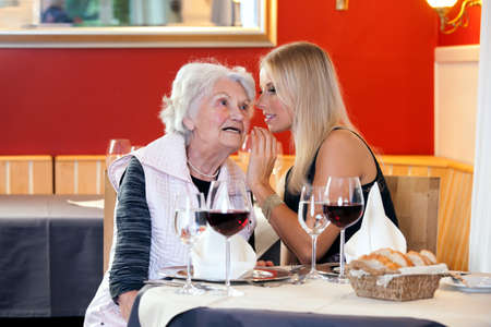 telling: Old and Young Women Talking at Restaurant Table with Glasses of Water, Wine and Mini Basket of Bread Stock Photo