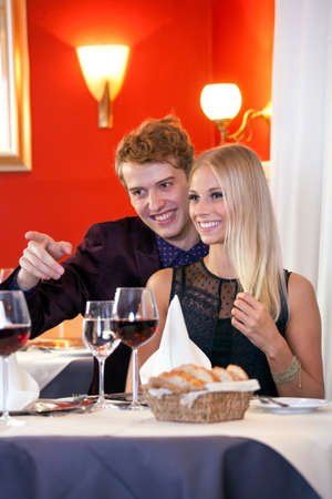 other side: Smiling Sweet Young White Couple Looking at Other Side in Restaurant During their Dinner Date.