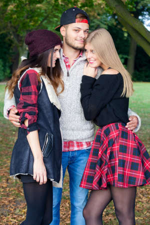 seducing: A male student is flirting with two female friends on a warm autumn day in a park. Stock Photo