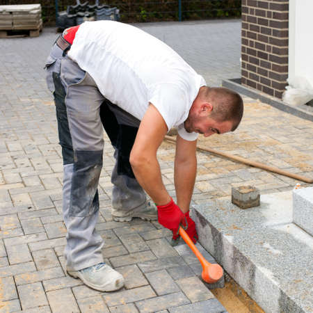 porches: Construction worker placing concrete paving stones to build up a pavement and a terrace in front of a house.