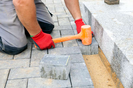 Bricklayer places concrete paving stone blocks for building up a patio and a track in the backyard of a private house.