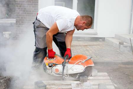 Trabajador de la construcción con una sierra de concreto, corte de piedras en una nube de polvo de concreto para la creación de una pista.