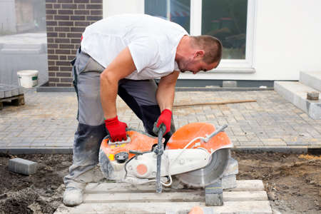Worker with concrete saw in his hands, cutting concrete paving stones for creating a terrace. photo