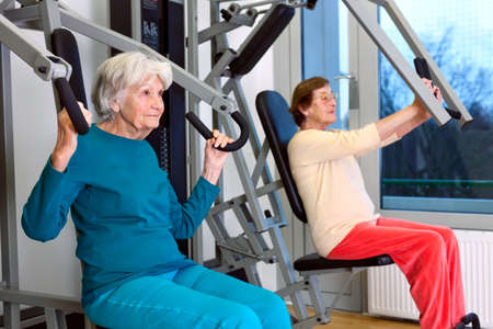 emphasizing: Two Senior Women Doing Chest Press Exercise at the Fitness Gym, Emphasizing Healthy Lifestyle.