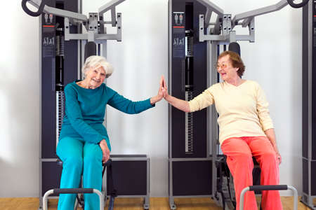 pres: Happy Healthy Old Women Doing Seated Chest Pres Exercise at the Fitness Gym, Touching by Palms After.