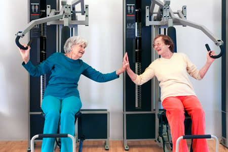 grannies: Happy Grannies Enjoying Chest Press Exercise, as if Playing, While Touching Their Palms and Looking Each Other. Stock Photo