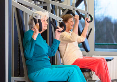 Side View of Serious Healthy Elderly Ladies in Chest Press Exercise at the Fitness Gym.
