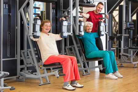 women working out: Smiling Elderly Women Working Out at the Fitness Gym with their Male Instructor, Looking at the Camera.