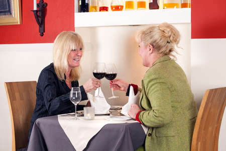 camaraderie: Two blond woman toasting each other with red wine as they sit enjoying a relaxing dinner in an upmarket restaurant
