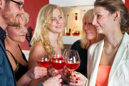 social gathering: Close up White Friends Tossing Glasses of Red Wine in a Social Gathering. Stock Photo
