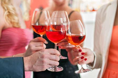 Close-up shot van Vrienden Werpen van glazen rode wijn in een partij.