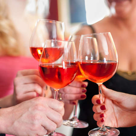 social gathering: Macro Shot of Hands Raising Glasses of Tasty Red Wine in a Social Gathering. Stock Photo