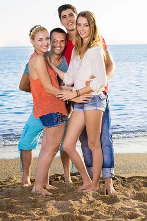clima tropical: Muy Cerrar felices j�venes amigos de pie en la arena en la playa en un clima tropical.