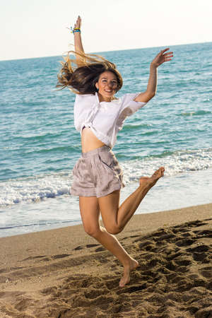 Full Length of Happy Young Woman Jumping at the Beach with Arms Raised on a Windy Tropical Climate.