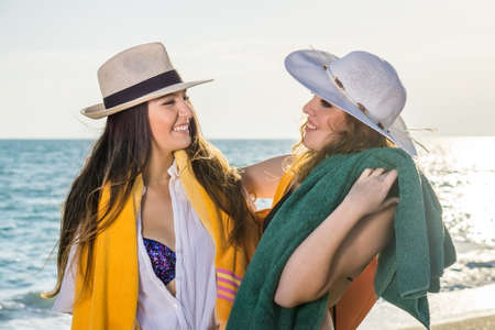 jaunty: Close up Pretty Young Girls in Summer Clothing at the Beach Smiling Each Other on One Sunny Day. Stock Photo