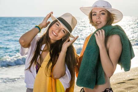 clima tropical: Cierre de las se�oras atractiva que presenta en la playa con sus sombreros de verano en un clima tropical.