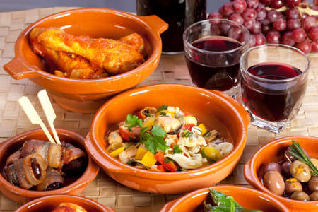 Different spanish appetizers, tapas including dates in bacon, seafood salad, chicken in tomato sauce and pickled olives, red wine and grapes.
