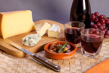vins: Glasses of red wine and mediterranean appetizers as italian antipasti or french starters � different kinds of cheese, olives and rosemary, two glasses of red table wine. Stock Photo
