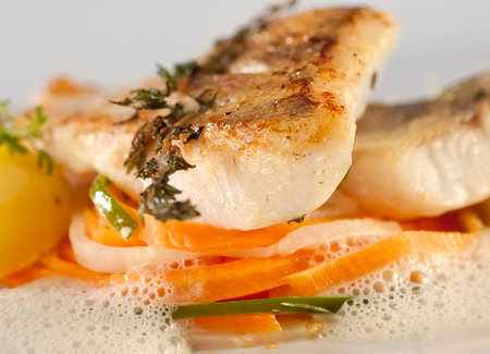Fried pike perch with vegetables on a bed of thin sliced stripes of carrots, cucumber and asparagus in a fluffy sauce, served with potatoes.