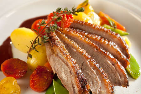 Roasted duck in slices with port wine sauce. Served with thyme and cherry tomatoes, potatoes, carrots and asparagus.