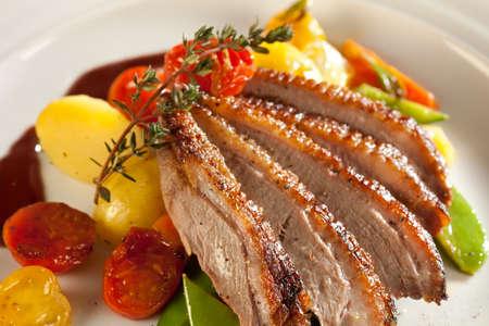 Geroosterde eend in plakjes met portsaus. Geserveerd met tijm en cherry tomaten, aardappelen, wortelen en asperges. Stockfoto