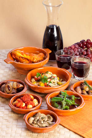 Traditional spanish tapas in terracotta bowls. Stock Photo