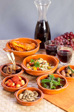 Collection of tapas foods including dates in bacon, butter beans with chorizo, mushrooms, seafood salad, chicken in tomato sauce and pickled olives and red wine.