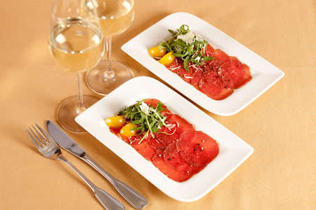 thinly: Carpaccio, dish of raw beef meat, thinly sliced and decorated with rocket, parmesan cheese and yellow cherry tomatoes. Served as appetizer in restaurant with two glasses of white wine.