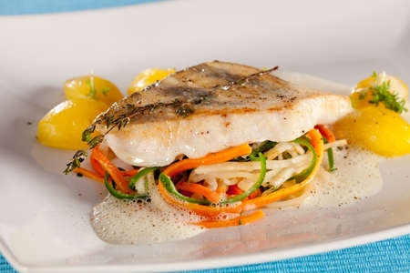 White fish filet of perch in fluffy sauce, decorated with thyme.