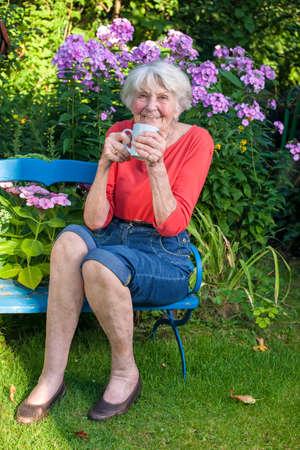 幸せな老婆になって庭で青いベンチでコーヒーのカップを閉じる