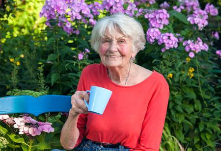 old age: Close up Felice la nonna in camicia rossa con una tazza di caffè in giardino con fiori piante sullo sfondo.