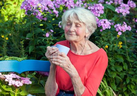 Close-up Doordachte oude vrouw genieten van de geur van haar koffie in het Garden. Stockfoto