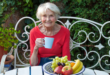 Close up Smiling Old Woman Having a Cup of Coffee at the Garden Table with Fresh Fruits Stock Photo