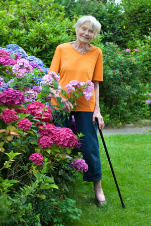 Full Length Portrait of Smiling Senior Woman Standing at the Flower Garden with Cane.