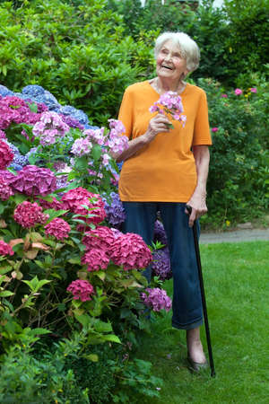 Full Length Shot of Thoughtful Old Woman Standing at the Garden with Flowers on Hand While Looking Up