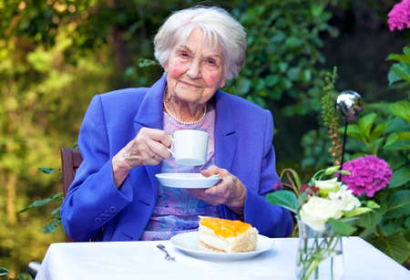 Close up Smiling Elderly Woman in Blue Violet Business Suit Holding a White Coffee Cup While Sitting at the Garden Table with a Slice of Cake, Looking at the Camera.